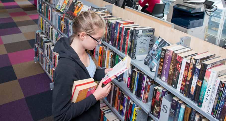 Teenage girl browses books