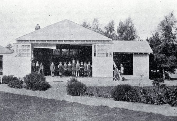 By the 1920s most parents were being guided by the Plunket Society to realise the benefits of fresh-air and sunlight for their children and the Christchurch Open-Air League had been able to persuade the Canterbury Education Board to build some open-air classrooms. The most common type was like this one at Fendalton School, Christchurch, where on sunny days, sliding doors allowed one whole wall to be opened to allow in fresh air and sunshine. Each pupil had a desk and chair which could be carried outside in fine weather. The porch on the right-hand side of the photograph served as a cloakroom and shelter-shed